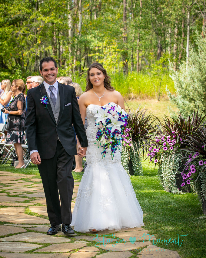 the bride and groom walk back up the stone path as the newest Mr and Mrs