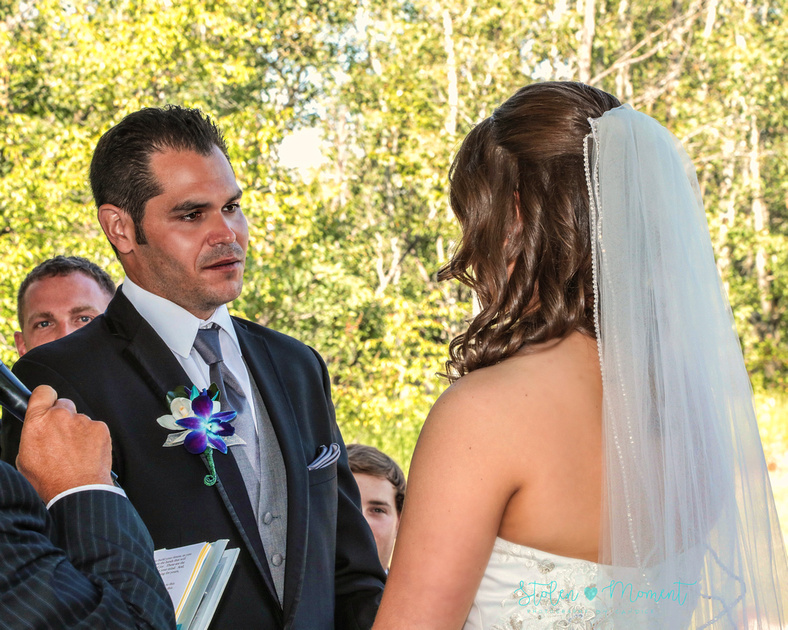 the groom looks into his bride's eyes as he says his vows