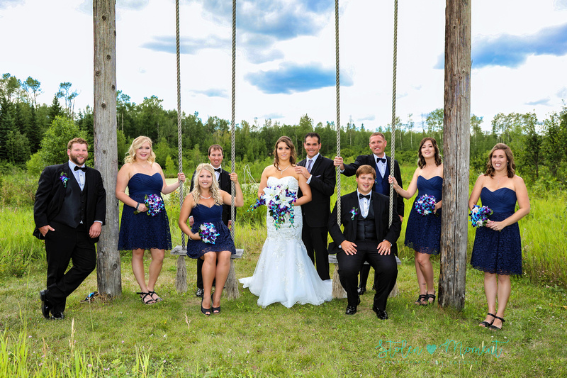 a wedding party of ten stand and sit around a wooden swing set at Hastings Lake Gardens, Sherwood Park