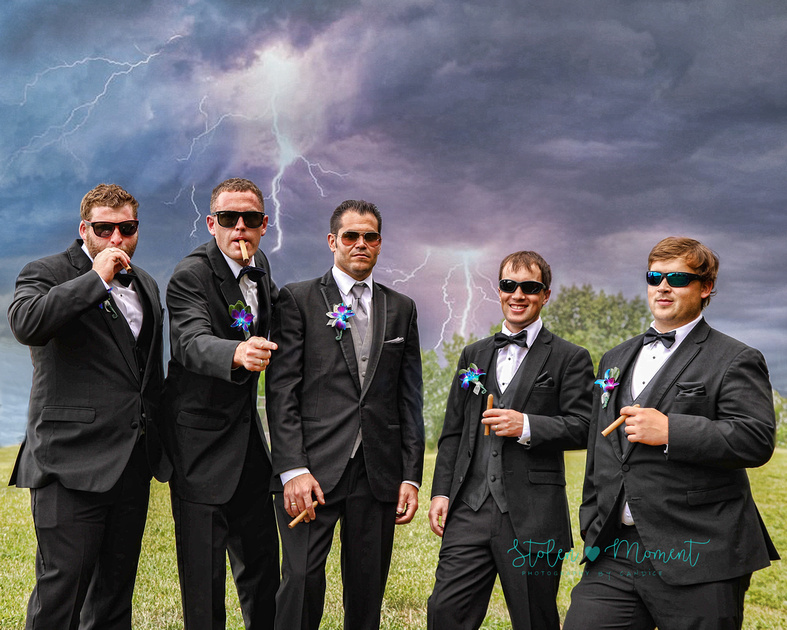the groom and his four groomsmen all wearing sunglasses and holding cigars pose seriously while the sky is menacing looking overhead