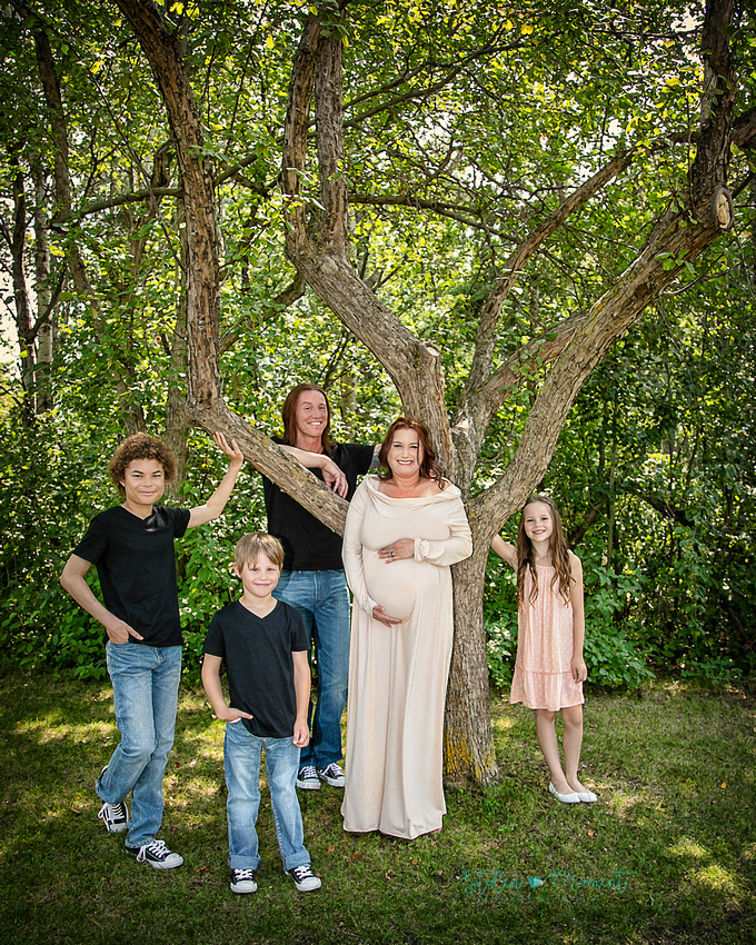 a Dad, expectant mom and their two sons and daughter stand around a tree in Hawrelak Park