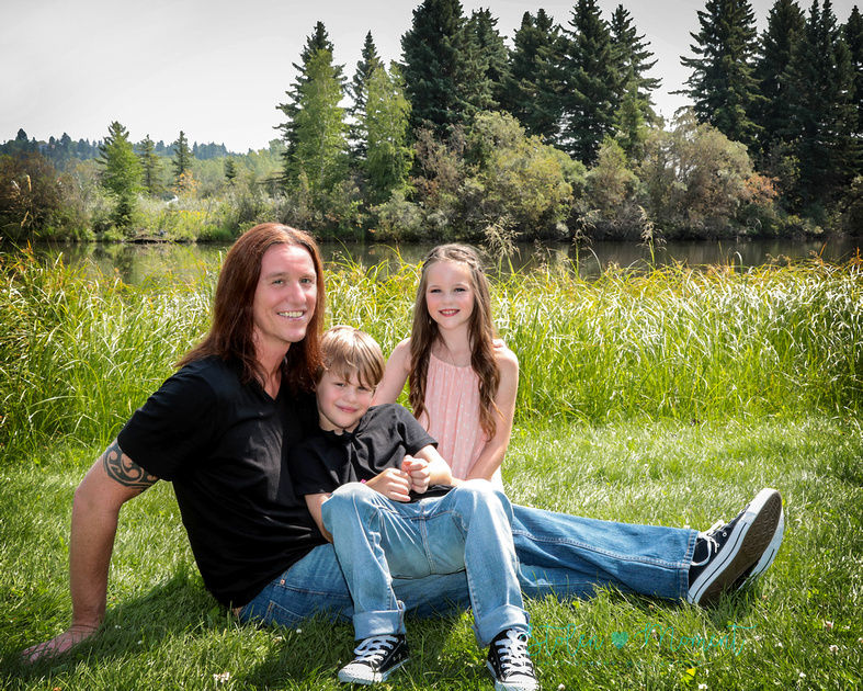 a dad sits on the grass by the lake with his son and daughter at William Hawrelak Park