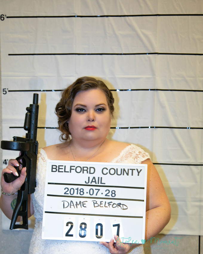 """the bride holds a """"country jail"""" sign, holds a Tommy gun in the other hand and has her mug shot taken during the reception"""