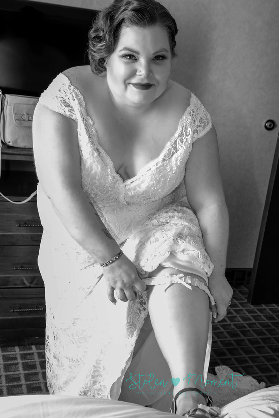 the bride looking very 1920ish with her hair and dress, rests her leg on the bed to put on her garter