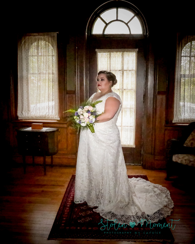 the bride stands in front of a glass door and windows looking very elegant at Rutherford House