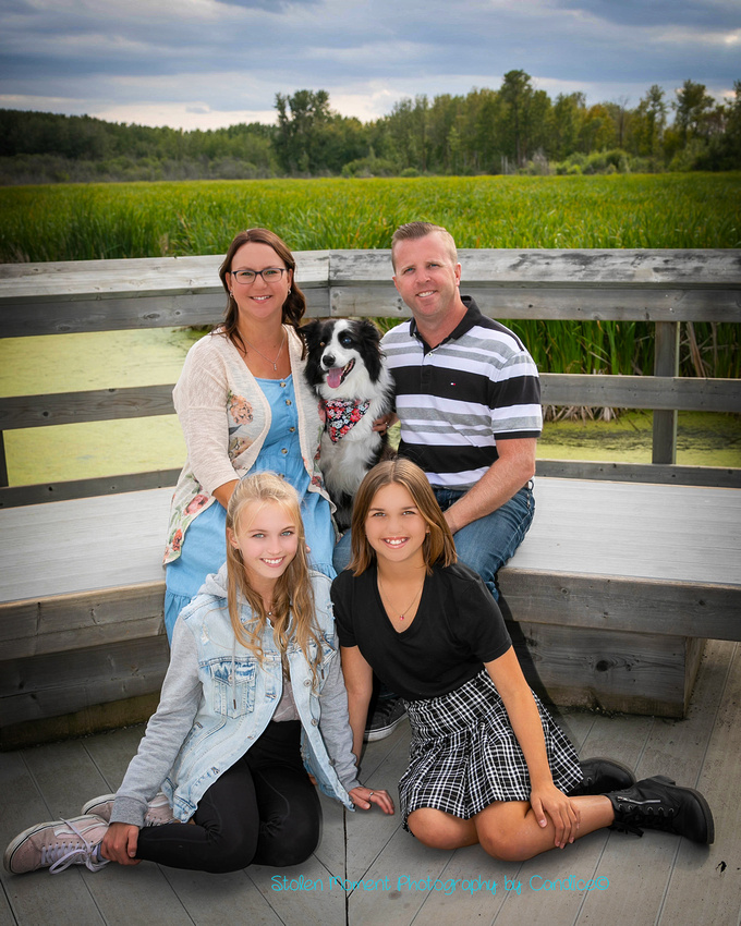 a beautiful family of four and their dog pose for photos around Lois Hole Centennial Provincial Park