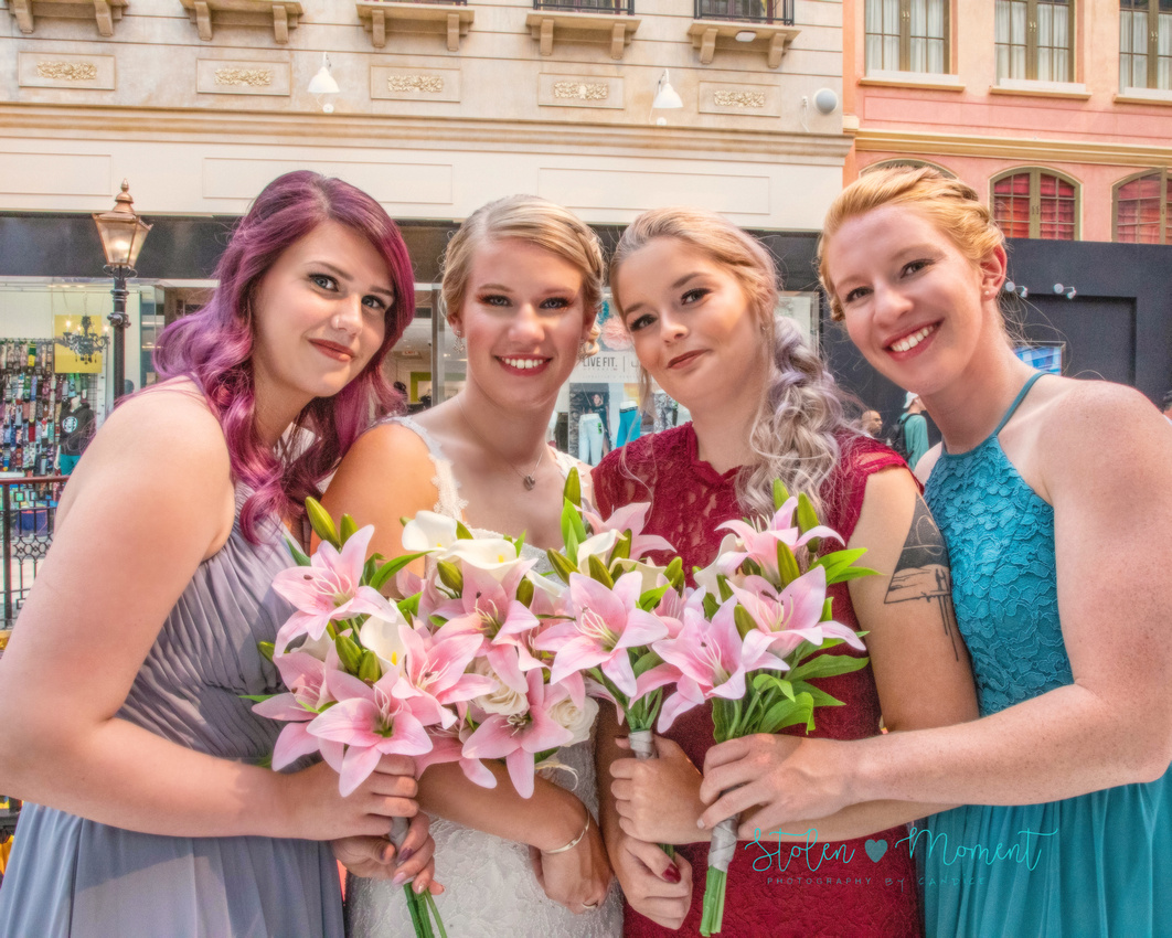 the bride and her three bridesmaids stand tightly together in front of the shops on Europa Blvd in West Edmonton Mall