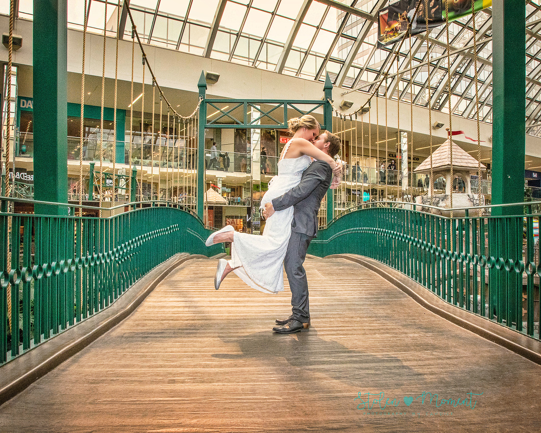 the groom lifts the bride in the air as they share a kiss on the bridge at West Edmonton Mall