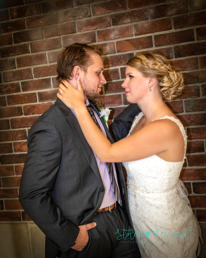 the bride and groom stand in front of a brick wall at West Edmonton Mall and share a look of love between them
