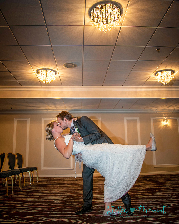 the groom dips his bride and shares a kiss with her underneath the chandeliers in a conference room at Fantasyland Hotel