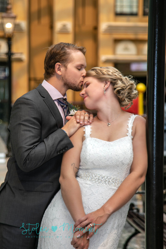 the groom gives his bride a kiss on her forehead as she leans on a lamp post on Europa blvd in West Edmonton Mall