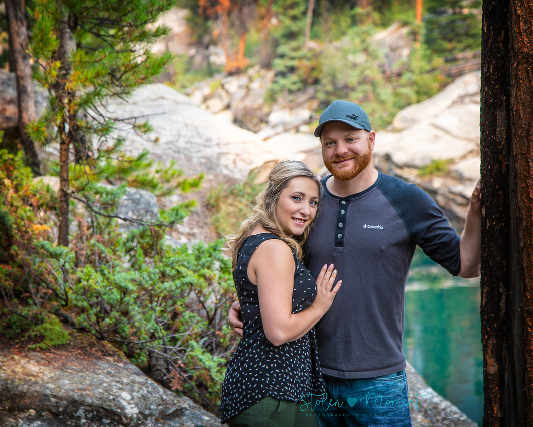 engaged couple pose among the rocks and water at Horseshoe Lake in Jasper National Park