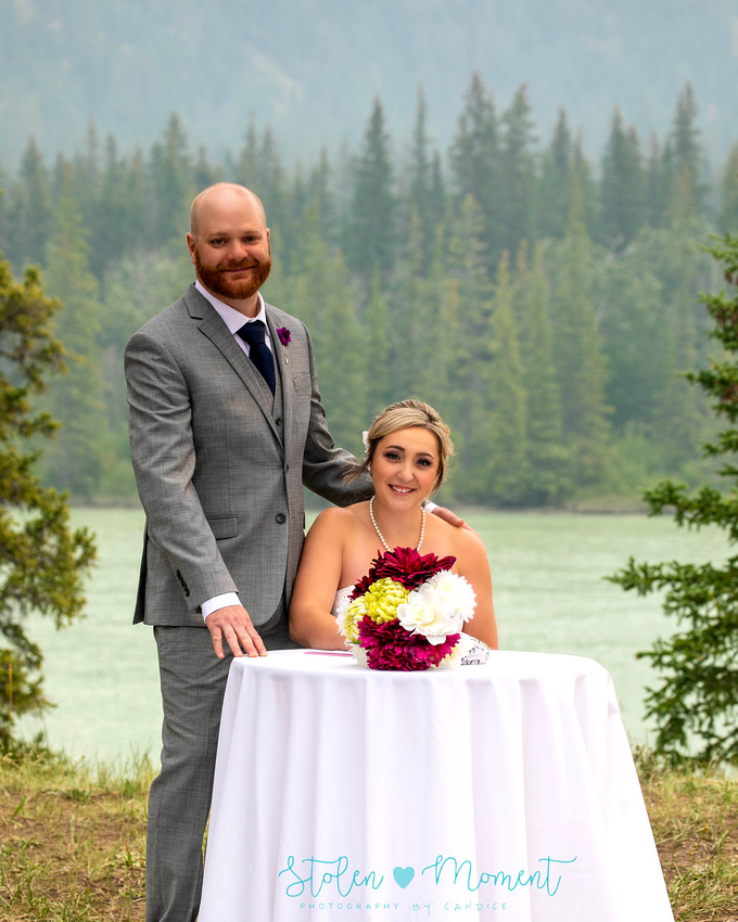 bride, groom and their wedding party pose around Jasper National Park