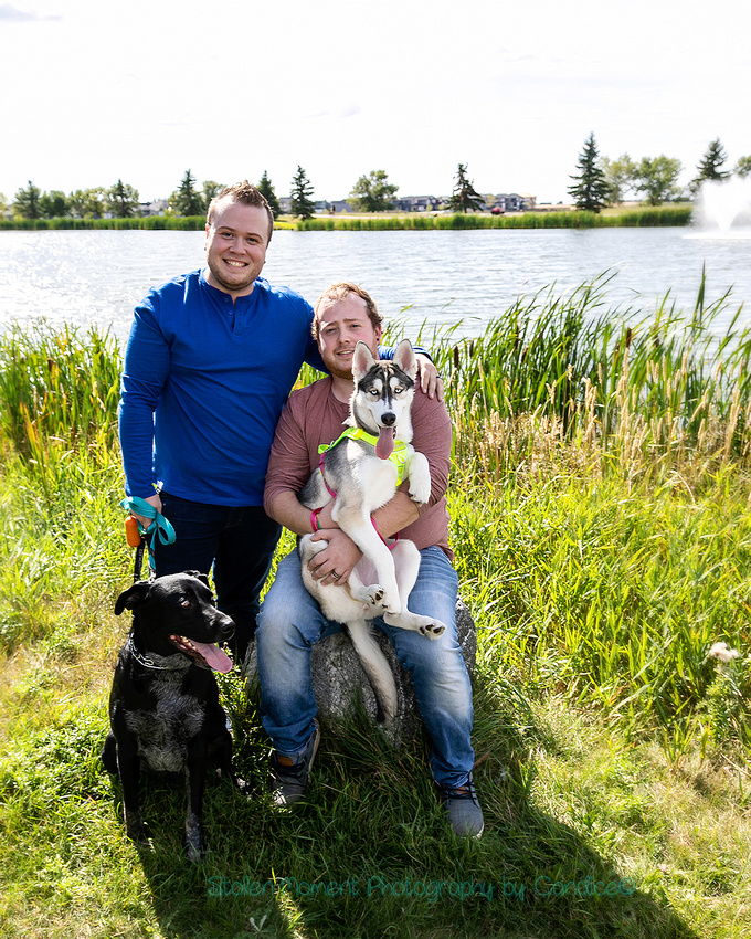 two guys and their two dogs pose for photos at a park in Beaumont for their engagement photos