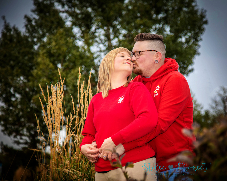 an engaged couple pose for photos at Festival Place in Sherwood Park