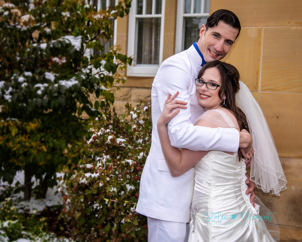 a bride in an elegant wedding dress and a groom in a white Indian suit are married at The Freemason hall in Edmonton with formals at Government House and Roger's Place on a snowy September day.