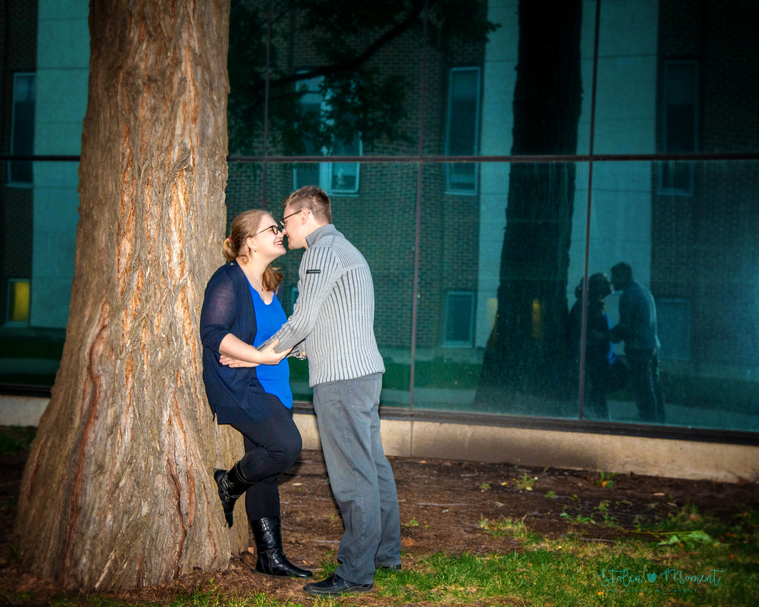 An engaged couple pose among the fall colours at the University of Alberta grounds