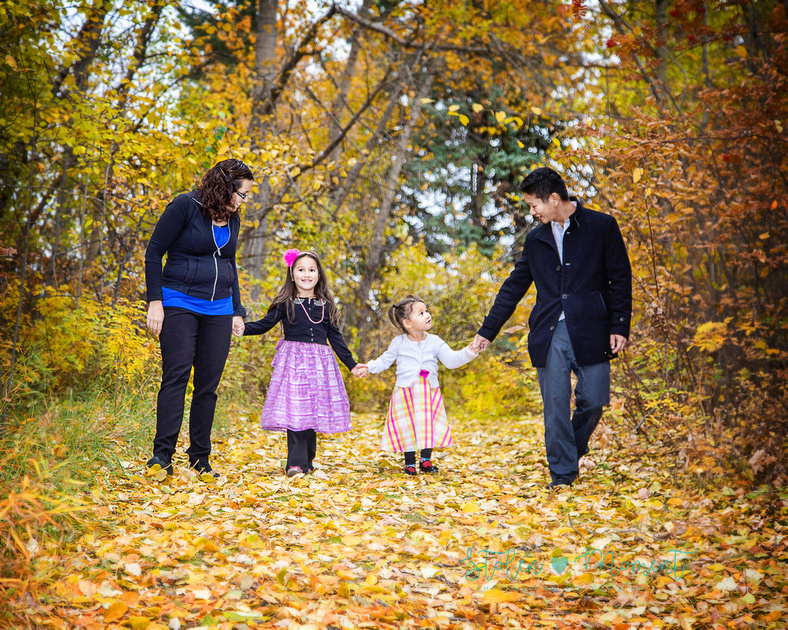 A Family of four poses among the beautiful fall colours at Hawrelak Park