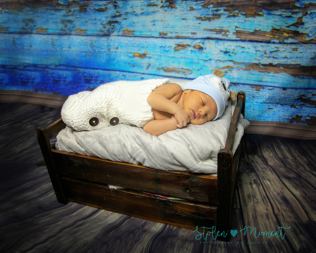 a two week old baby boy sleeps atop a photography prop bed