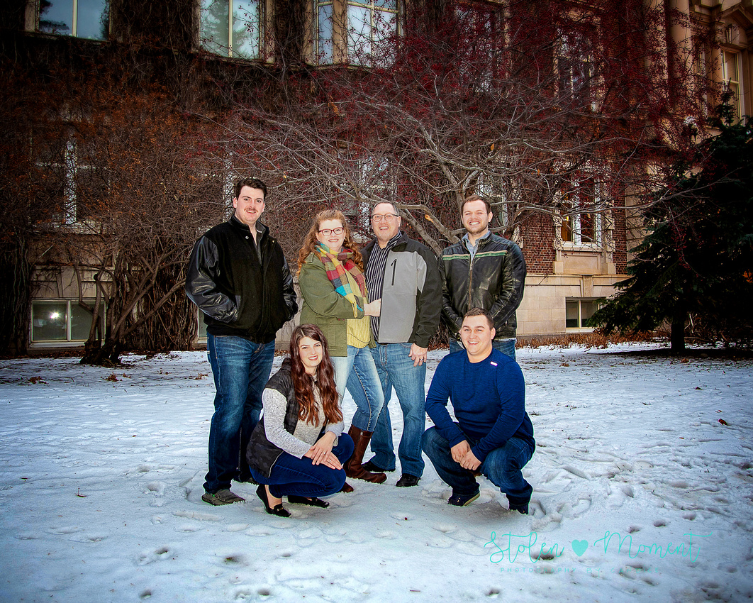 a family of six pose outside of convocation hall in the snow for photos