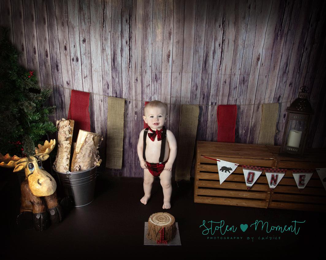 One year old birthday boy having a lumberjack birthday cake smash