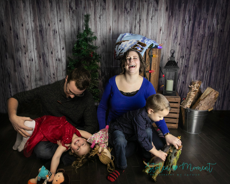 A family of four sit for a studio family photography session