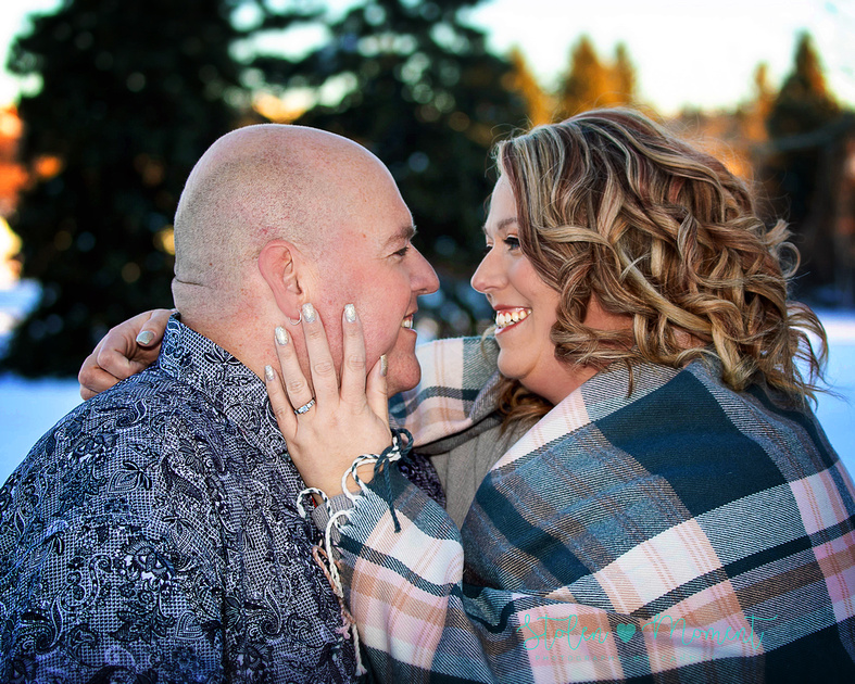 An engaged couple pose in the snow at Hawrelak Park for their engagement photos