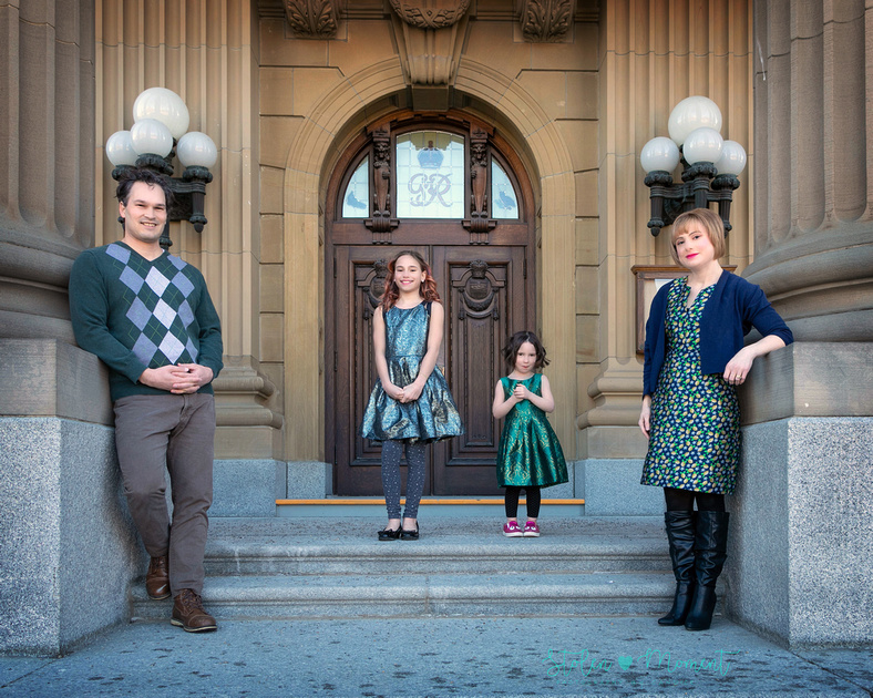 a mom, dad and their two daughters being photographed at the Alberta Legislative grounds