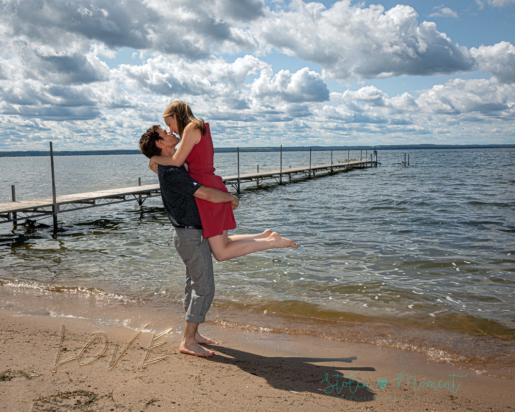 a stunning engaged couple at Pigeon Lake for their engagement session pose in the trees and lake side.