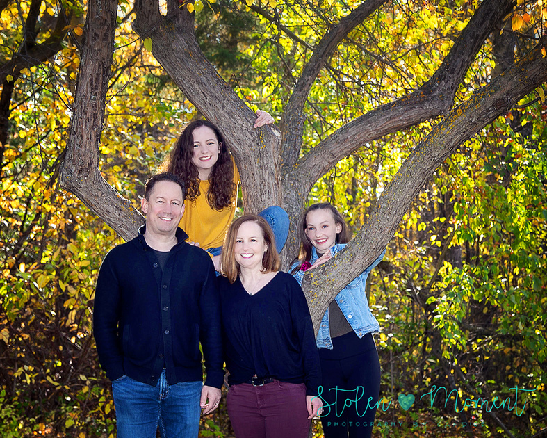 a Mom, Dad and their two teenage daughters pose for photos around the fall trees and leaves at Hawrelak Park