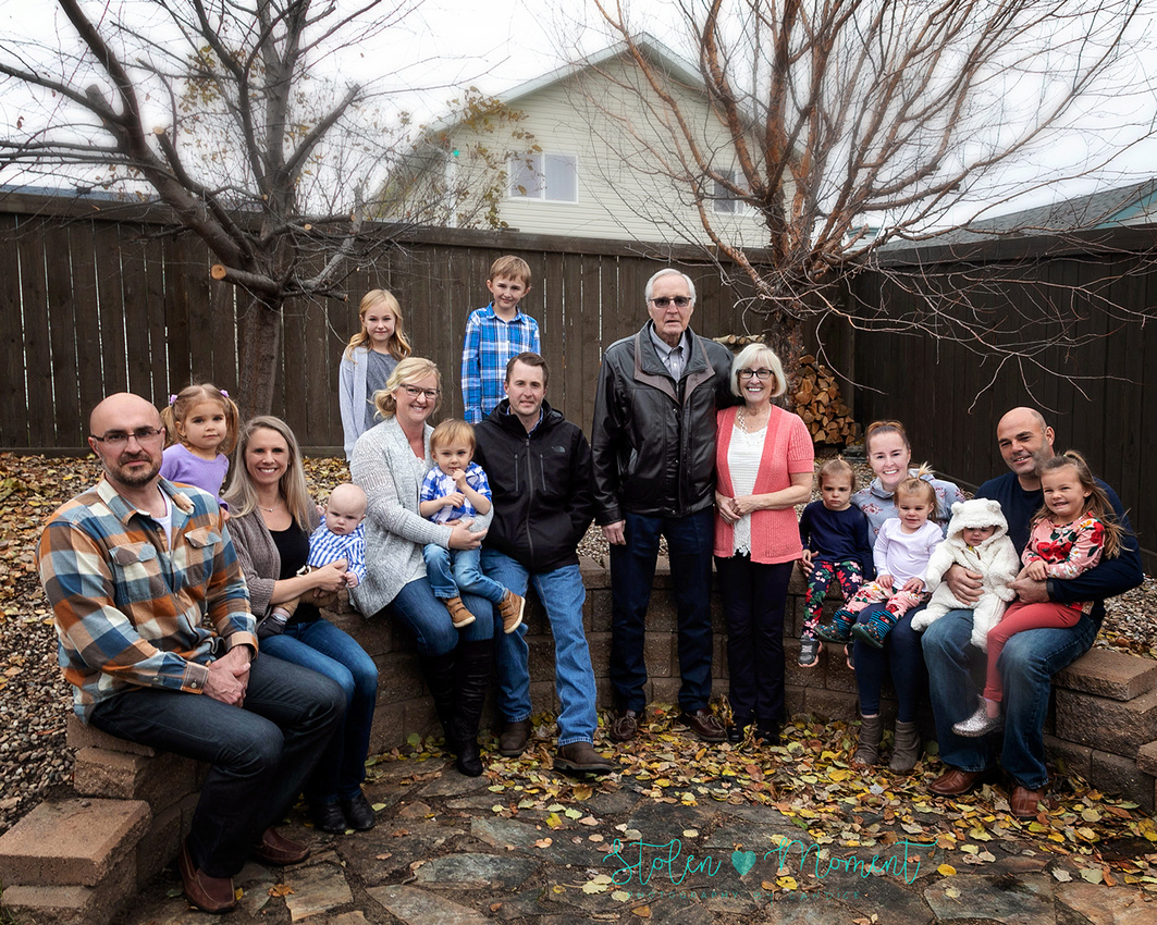 Family of fifteen photographed on a chilly fall afternoon in a Stony Plain backyard.