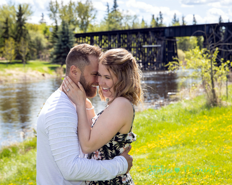 a beautiful couple pose for engagement photos at a local park in St. Albert