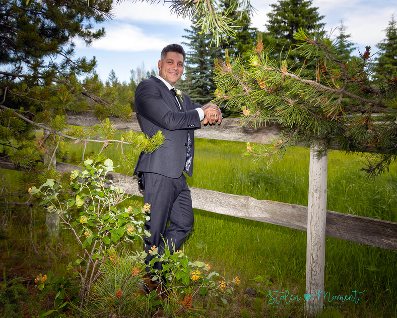 A groom leans on a fence during his country wedding