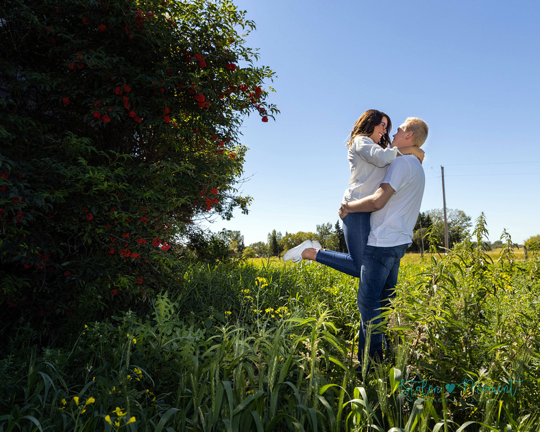 An engaged couple have their photos taken at a rustic barn in Strathcona county