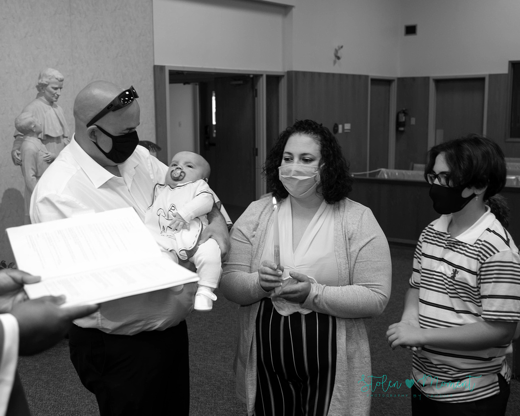 a three month old boy is baptized in church surrounded by family