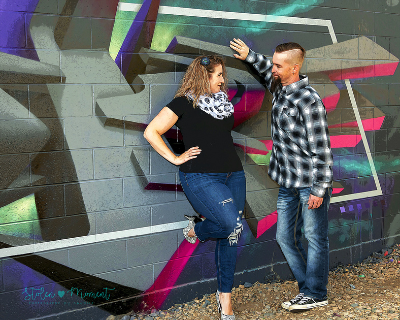 A fun couple with their three children pose for engagement and family photos at a graffiti wall in Edmonton