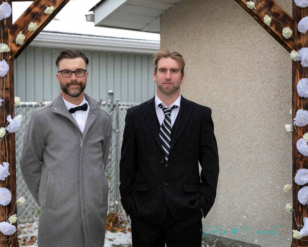 bride and groom are married in a backyard wedding with the snow falling in Leduc