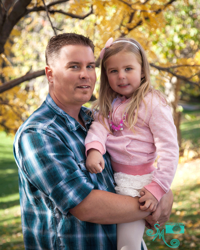 dad and his little girl smile at camera with fall leaves in background