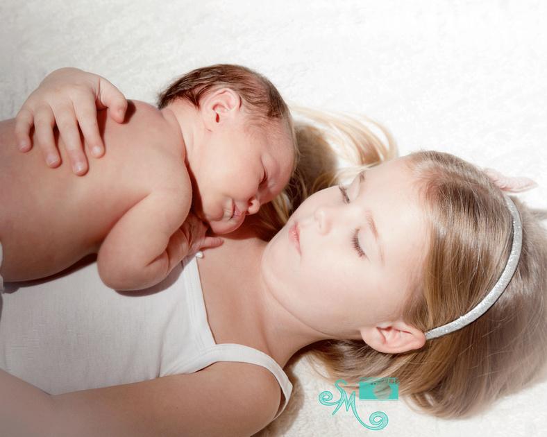 Beautiful newborn baby girl snuggled into her big sister