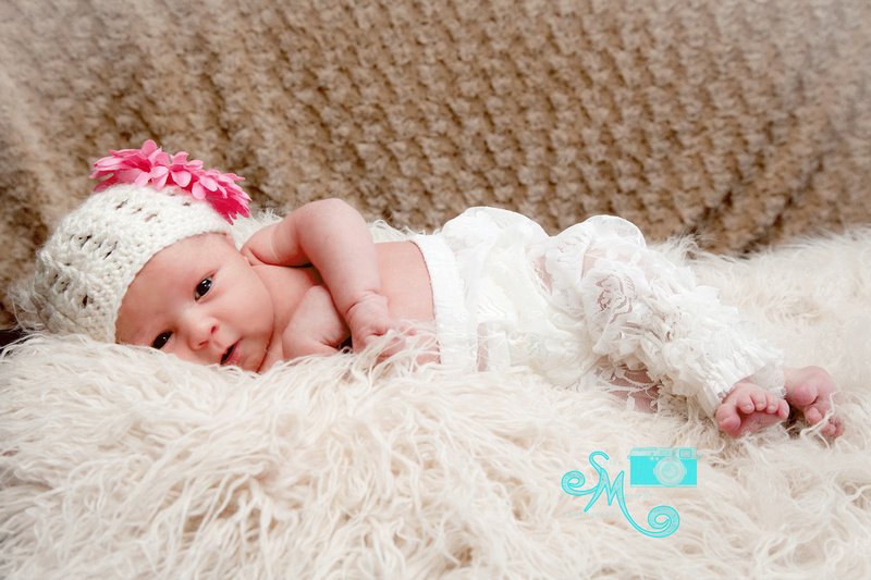 a newborn lays on her side looking into camera