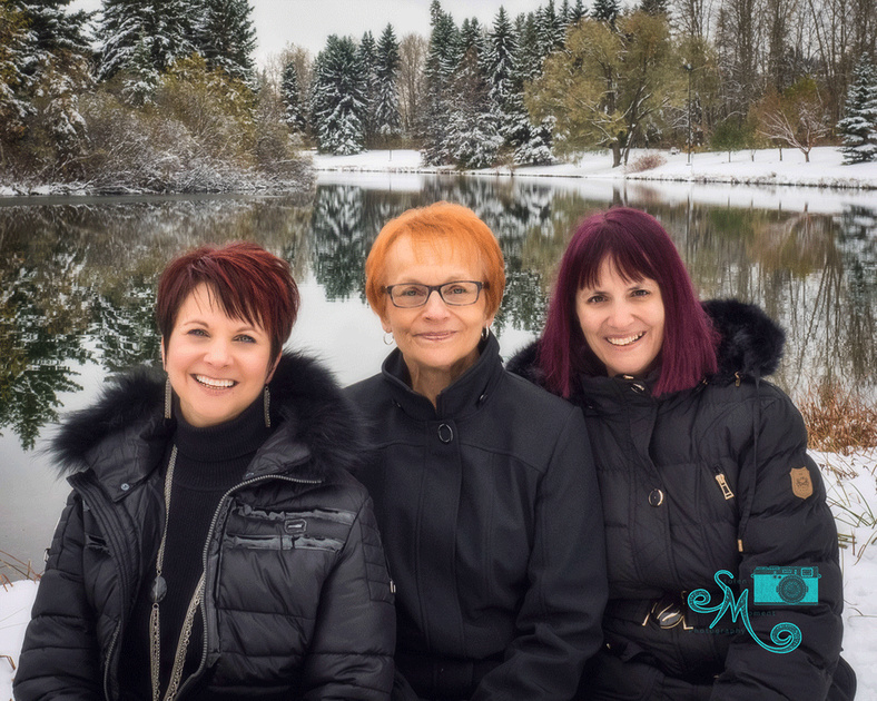 a mother and her two grown daughters pose in front of the lake at Hawrelak park