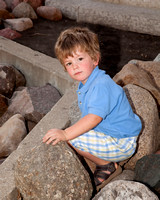 photo of little boy sitting on rocks