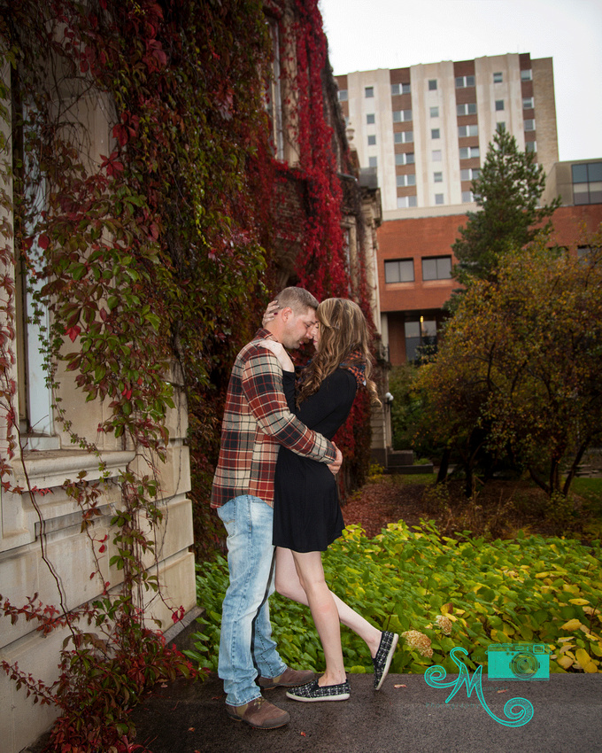 an engaged couple embrace on steps of Convocation hall at U of A with vivid red vines in background