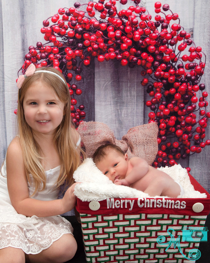 a newborn sleeps in a Christmas box and her big sister sits beside her in a Christmas themed photo