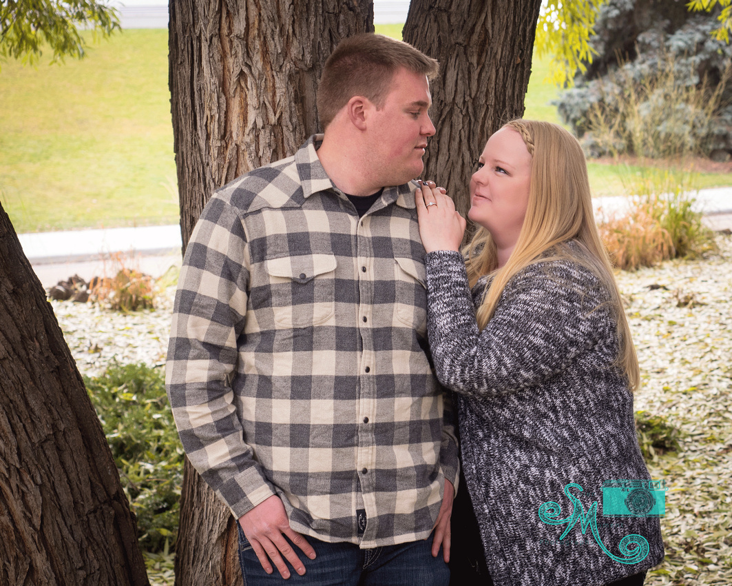 a woman looks adoringly at her fiancé while posed against a tree