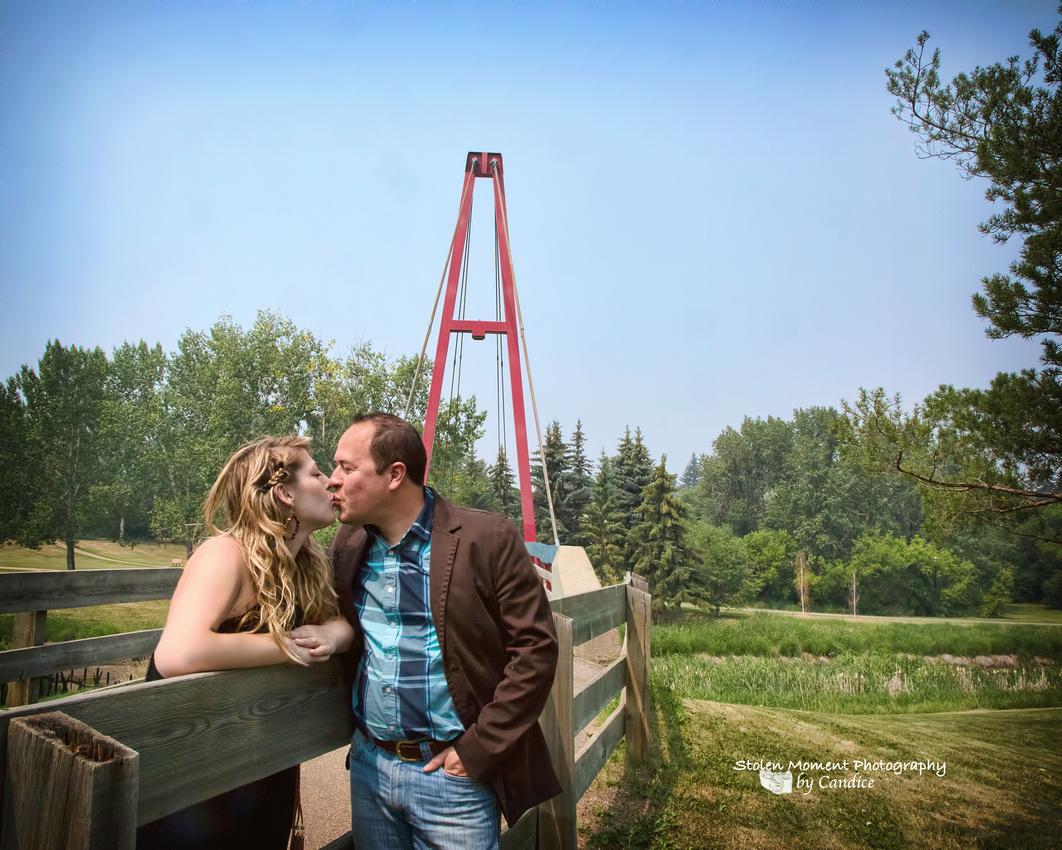 engaged couple kissing with bridge in background