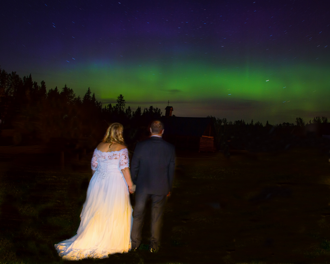 Bride and groom watching northern lights