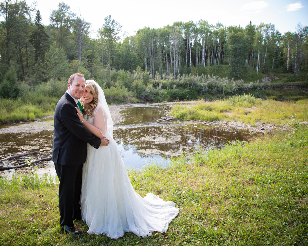 bride and groom in front of Alberta slough