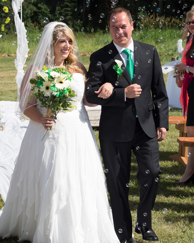 Bride and Groom walking back down aisle with bubbles being blown