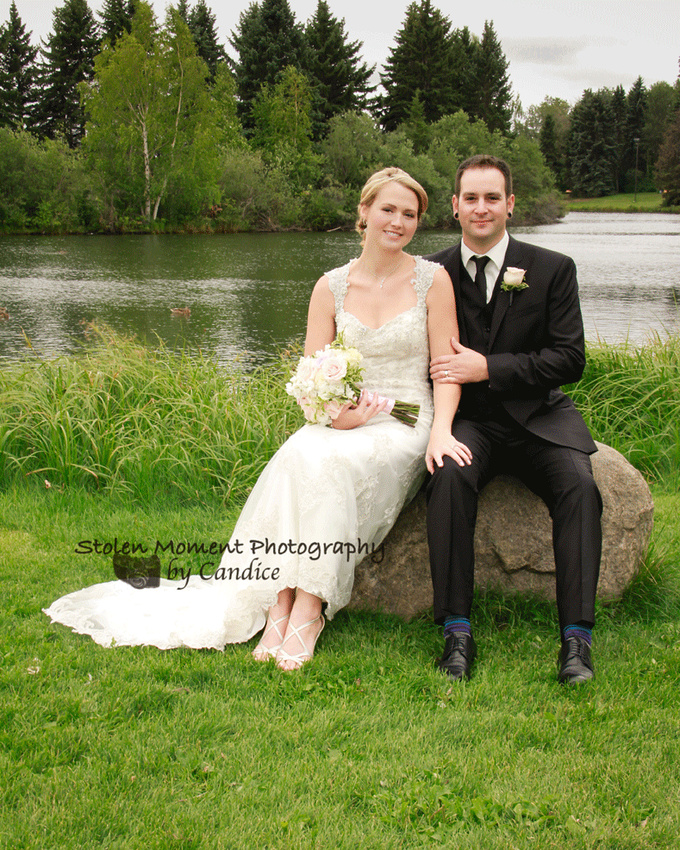 bride and groom on rock in hawrelak park